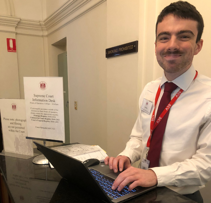 A Supreme Court staff member acting as concierge at the Supreme Court entrance of 210 William Street.