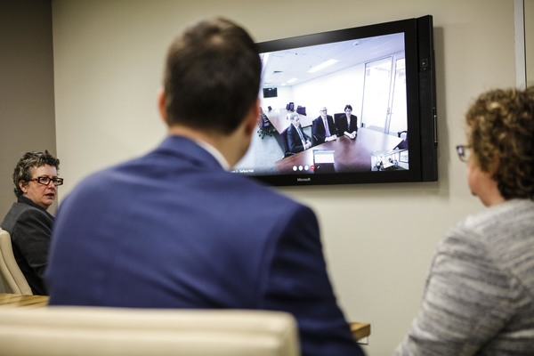 A group of mediators of the Supreme Court in a mediation room , communicate with another group of people using video conferencing.
